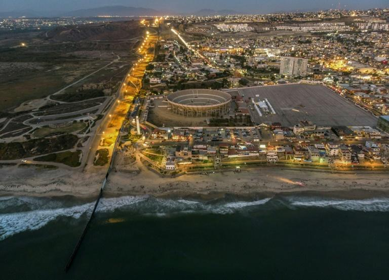An aerial view of the United States (L) - Mexico (R) border fence extending into the Pacific ocean at Playas de Tijuana, Mexico