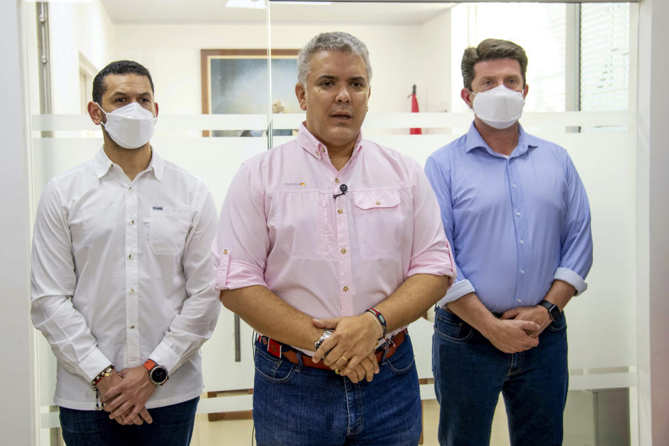 In this photo released by Colombia's Presidency, President Ivan Duque speaks, flanked by Interior Minster Daniel Palacios, left, and Defense Minister Diego Molano, in Cucuta, Colombia, Friday, June 25, 2021. Duque said that the helicopter they were traveling on was attacked at the Catatumbo region, on the northeastern border with Venezuela. (Cesar Carrion/Presidency of Colombia via AP)