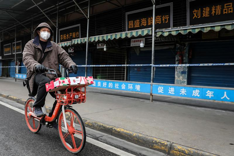 A man wears a mask while riding a bike past the closed Huanan Seafood Wholesale Market, which has been linked to the coronavirus in Wuhan, Hubei province, China on Jan. 17, 2020.   Getty Images