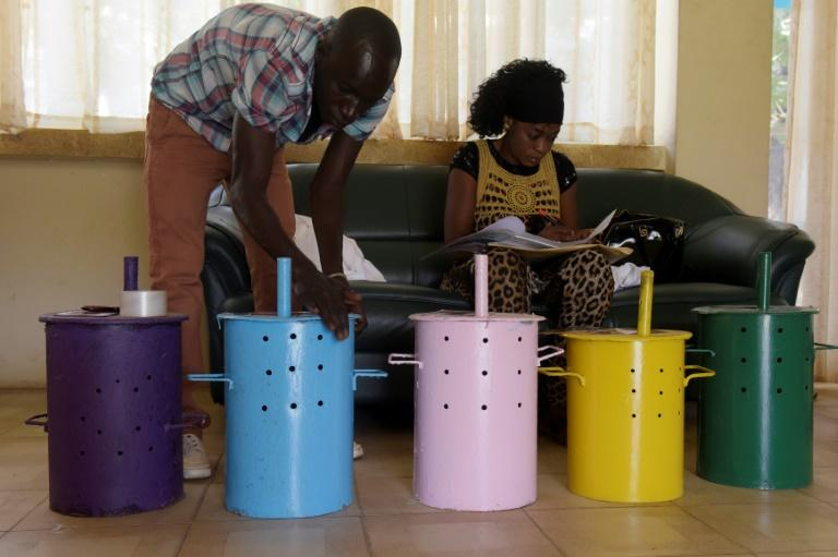Gambian polling agent prepare voting barrels at a polling station in Banjul on April 5, 2017, a day ahead of legislative elections
