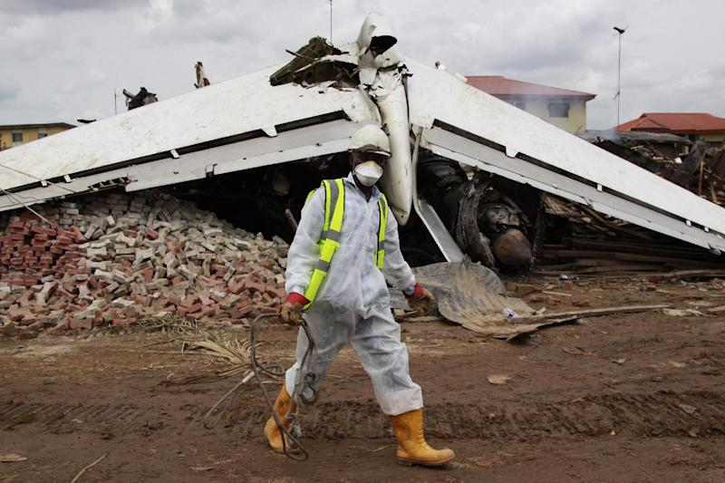 A rescue worker walks past the wreckage of a plane  in Lagos, Nigeria, Monday, June 4, 2012. The passenger plane carrying more than 150 people crashed in Nigeria's largest city on Sunday, government officials said. Firefighters pulled at least one body from a building that was damaged by the crash and searched for survivors as several charred corpses could be seen in the rubble. (AP Photo/Sunday Alamba)