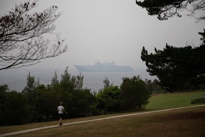 A man makes his way at the Eden Lookout as the Royal Australian Navy vessel HMAS Adelaide is covered by smoke in the town of Eden