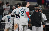 Miami Marlins manager Don Mattingly high-fives players after the team's 6-5 win over the Atlanta Braves in 10 innings in a baseball game Wednesday, April 14, 2021, in Atlanta. (AP Photo/Brynn Anderson)