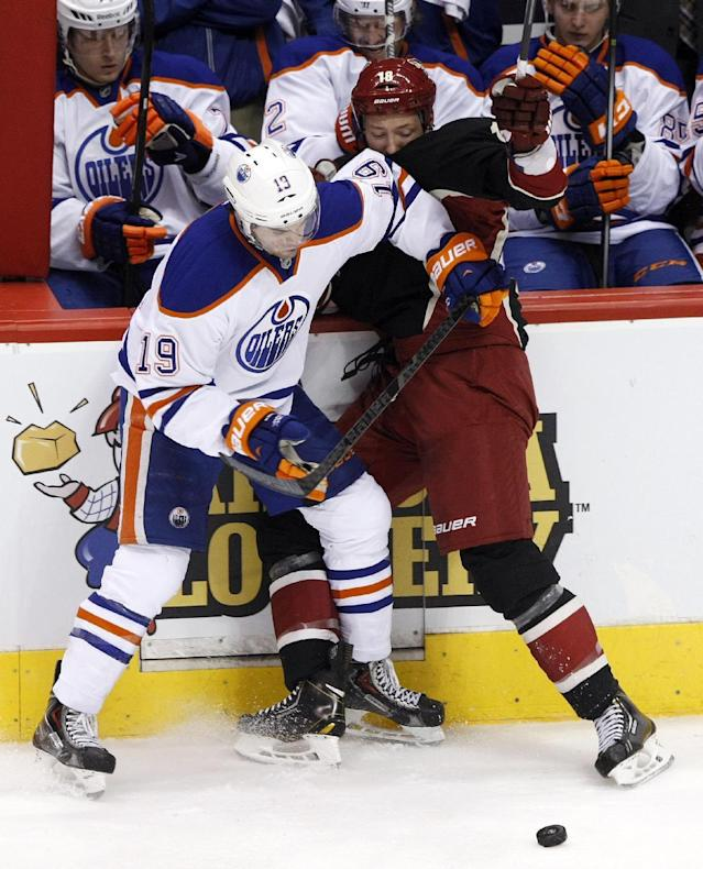 Edmonton Oilers defenseman Justin Schultz (19) and Phoenix Coyotes right wing David Moss battle for the puck in the second period of an NHL hockey game, Tuesday, Dec. 31, 2013, in Glendale, Ariz. (AP Photo/Rick Scuteri)
