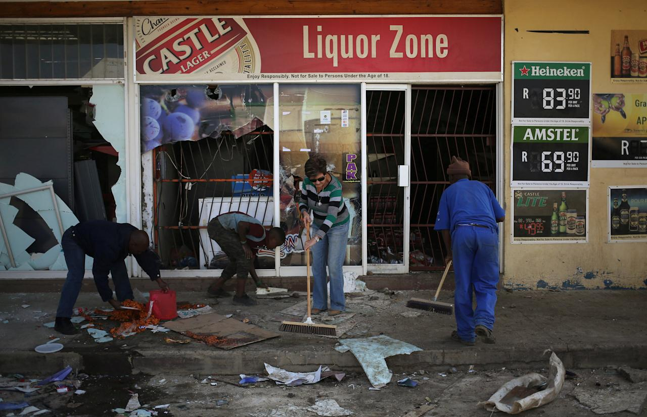 Locals clean up after over-night looting, when protesters took to the streets to demonstrate the killing of a boy in Coligny, North West province, South Africa, April 26, 2017. REUTERS/Siphiwe Sibeko     TPX IMAGES OF THE DAY