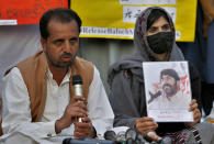 Nasrullah Baluch, left, leader of the Voice of Baluch Missing Persons, speaks while a woman holds portrait of her missing family members during a press conference in Islamabad, Pakistan, Saturday, Feb. 20, 2021. Dozens of relatives of Baluch missing persons, allegedly taken away by security agencies from restive Baluchistan province, Saturday ended their ten-day protest sleeping in the February cold near Pakistan parliament in capital Islamabad as minster for Human Rights assured their demand for recovery of loved ones would be taken seriously. (AP Photo/Anjum Naveed)