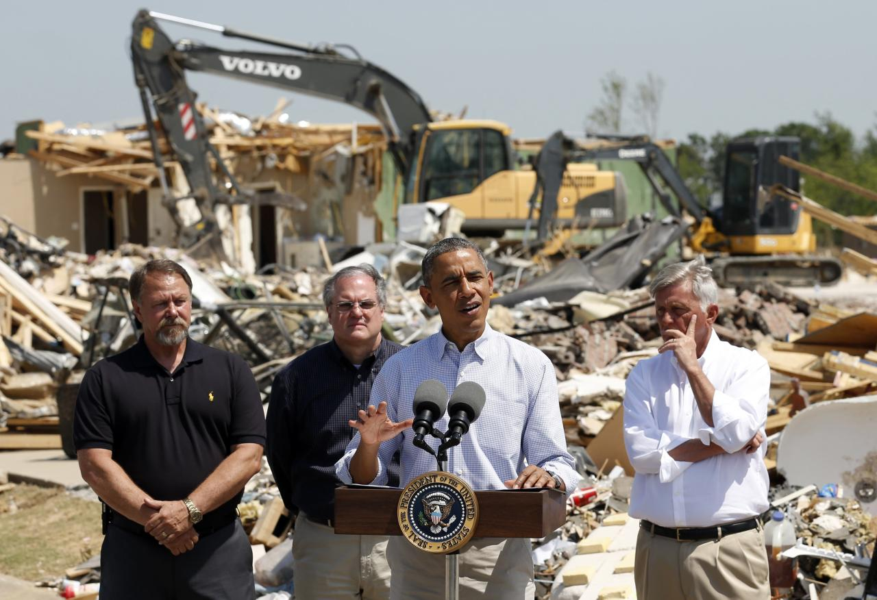 Amid the wreckage, U.S. President Barack Obama speaks as he visits the tornado devastated town of Vilonia, Arkansas May 7, 2014. With Obama are Vilonia Mayor James Firestone (L) Senator Mark Pryor (2nd L) and Governor Mike Beebe (R). The tornadoes were part of a storm system that blew through the Southern and Midwestern United States earlier this week, killing at least 35 people, including 15 in Arkansas. Obama has already declared a major disaster in Arkansas and ordered federal aid to supplement state and local recovery efforts. REUTERS/Kevin Lamarque (UNITED STATES - Tags: POLITICS DISASTER)