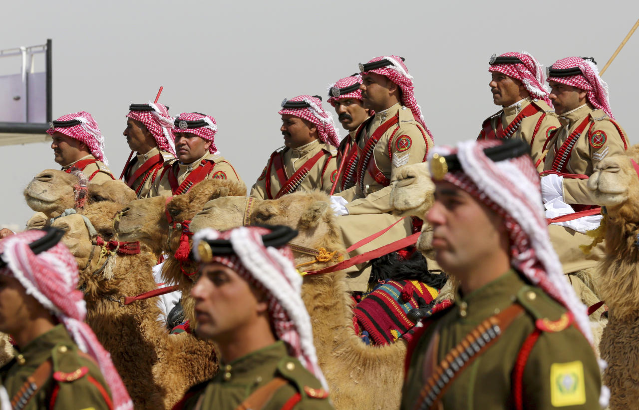 An honor guard on camel back greets Saudi Arabia's King Salman, not seen, in a lavish welcome ceremony complete with cannon salutes, Amman Jordan, Monday, March 27, 2017. Salman is in Jordan to attend the annual Arab Summit, to be held on Wednesday. Issues on the summit agenda include conflicts in Syria, Libya and Yemen. Saudi Arabia is an important financial backer of Jordan. (AP Photo/ Raad Adayleh)