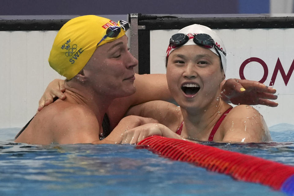 Margaret MacNeil, right, of Canada, is congratulated by Sarah Sjoestroem of Sweden after winning the final of the women's 100-meter butterfly at the 2020 Summer Olympics, Monday, July 26, 2021, in Tokyo, Japan. (AP Photo/Matthias Schrader)