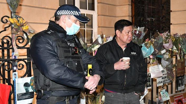 Myanmar ambassador to UK Kyaw Zwar Minn speaks to police officers after trying and failing to enter Myanmar's embassy in Mayfair, London
