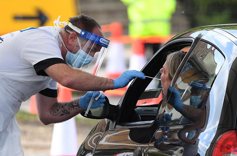 A medical worker takes a swab at a drive-in coronavirus testing facility at the Chessington World of Adventures Resort in south west London, as the UK continues in lockdown to help curb the spread of the coronavirus.