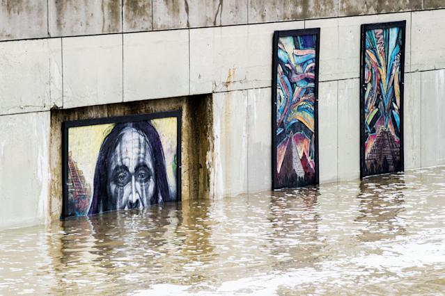 <p>The Flint River overflows onto artist renderings along what is normally a walkway as heavy rain causes flooding on Wednesday, Feb. 21, 2018 in Flint, Mich. (Photo: Jake May/The Flint Journal-MLive.com via AP) </p>