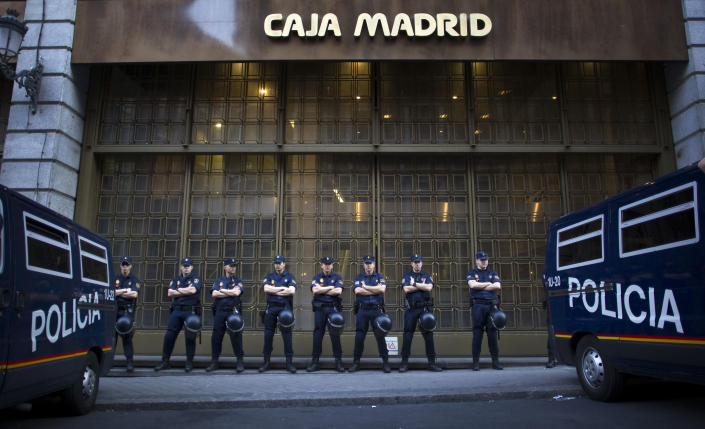 """File - In this May 14, 2012 file photo, riot police stand guard in front of a branch of the recently nationalized Caja de Madrid/ Bankia bank in Madrid. Spain's government said Friday Oct. 19, 2012 it is considering a ban on photographing, filming and reproducing images of police and state security forces while """"in the exercise of their functions."""" Deputy Prime Minister Soraya Saenz de Santamaria said that after months of television and internet viewing of sometimes violent clashes between police and demonstrators a balance had to be struck """"between citizens' right to protest"""" and a need """"to uphold the integrity of state security forces."""" (Alberto Di Lolli, File)"""
