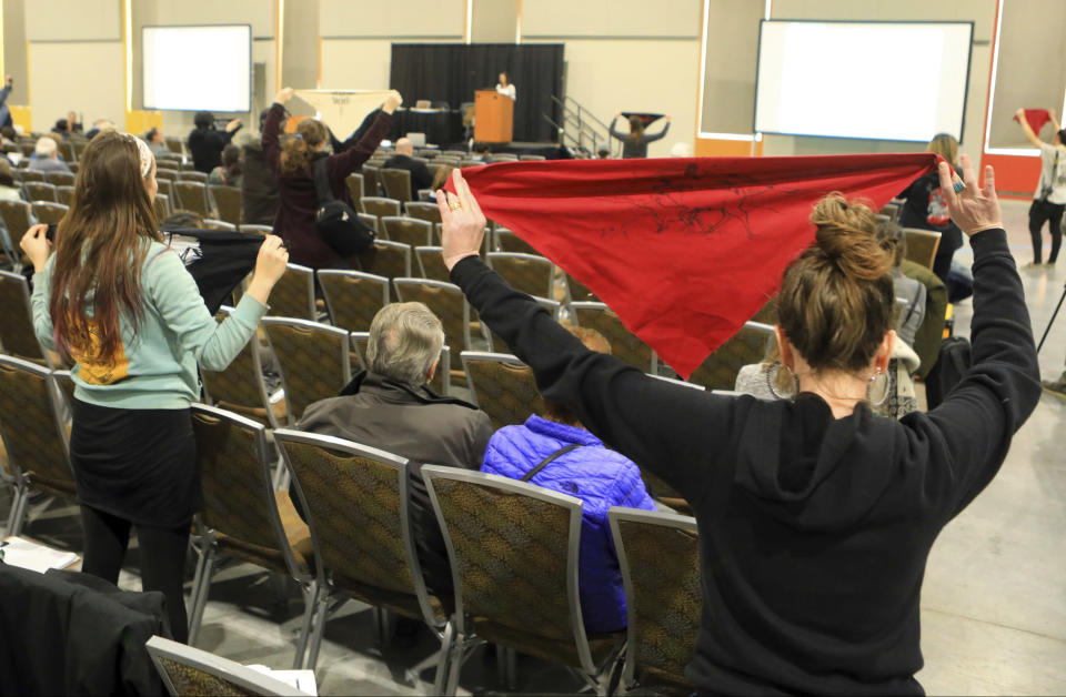 FILE - In this Feb. 11, 2019 file photo, protesters hold up flags during a public hearing on a draft environmental plan on proposed petroleum leasing within Alaska's Arctic National Wildlife Refuge in Anchorage, Alaska. Conservationists will try to persuade a U.S. judge to stop the Trump administration from issuing leases to oil and gas companies in the Arctic National Wildlife Refuge. The Anchorage Daily News reported that the videoconference Monday, Jan. 4, 2021, in U.S. District Court in Anchorage is expected to determine whether the Bureau of Land Management can open bids in an online lease sale scheduled for Wednesday. The agency has offered 10-year leases on 22 tracts covering about 1,563 square miles in the coastal plain, which accounts for about 5% of the refuge's area. (AP Photo/Dan Joling, File)