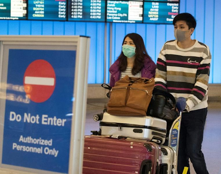 Passengers wear masks to protect against the spread of the novel coronavirus as they arrive at Los Angeles International Airport