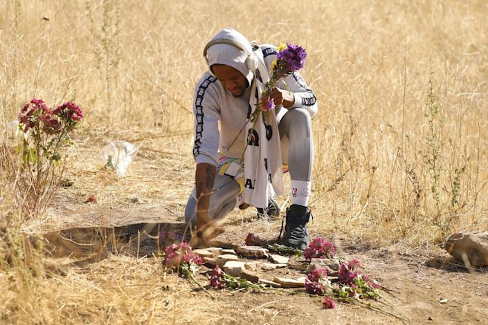 Dontate Matthews, 30, of Calabasas places flowers on rocks arranged to form the number 8 in Calabasas.