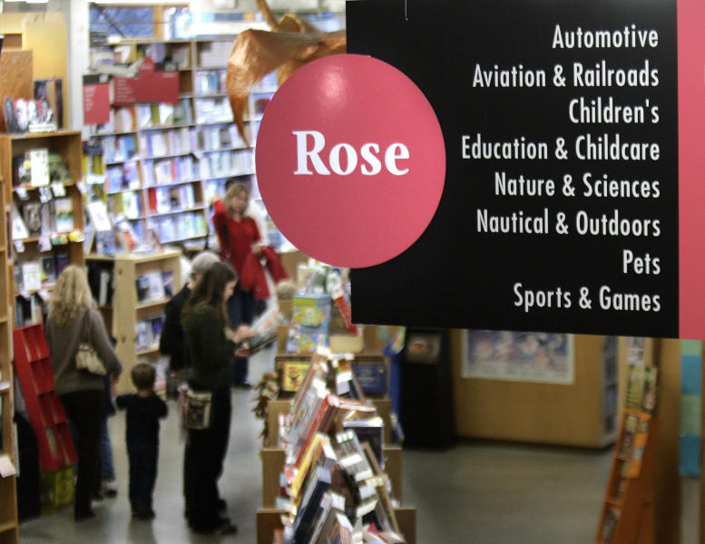 FILE - This Jan. 4, 2008 file photo shows people perusing books in the Rose Room at Powell's Bookstore in downtown Portland, Ore. A destination bookstore can make you feel like you're part of the community, whether you're grooving on the laidback vibe at Powell's or tuning into the Beltway buzz at Washington's Politics & Prose.(AP Photo/Don Ryan, file)