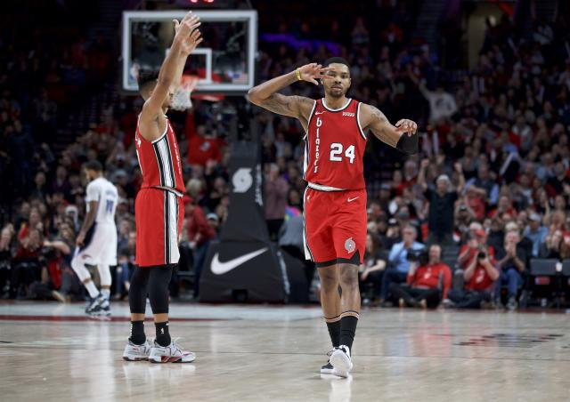 Portland Trail Blazers guard Kent Bazemore, right, and guard CJ McCollum react after Bazemore made a 3-point basket against the Orlando Magic during the second half of an NBA basketball game in Portland, Ore., Friday, Dec. 20, 2019. (AP Photo/Craig Mitchelldyer)