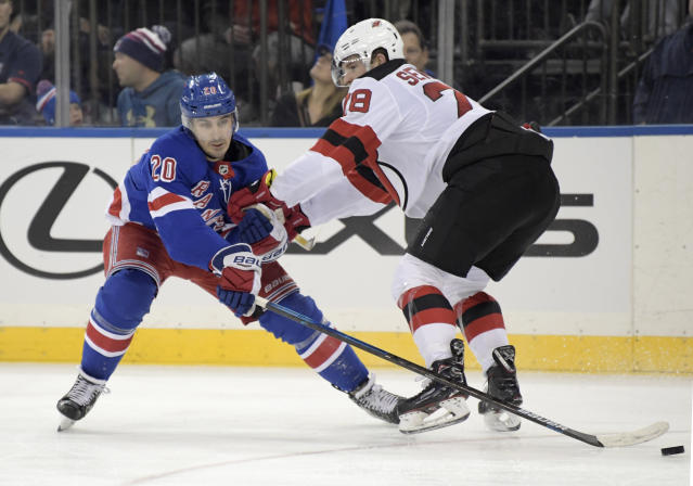 New York Rangers left wing Chris Kreider (20) reaches for the puck as he is checked by New Jersey Devils defenseman Damon Severson (28) during the second period of an NHL hockey game Saturday, Feb. 23, 2019, at Madison Square Garden in New York. (AP Photo/ Bill Kostroun)