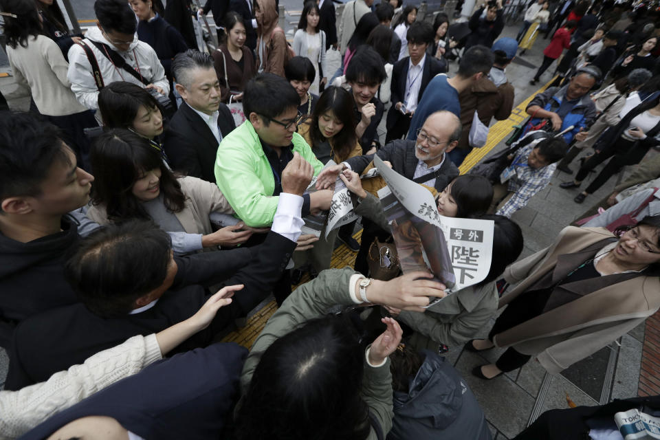 A Yomiuri newspaper worker hands a copy of the extra edition reporting the enthronement ceremony for the 59-year-old Emperor Naruhito Tuesday, Oct. 22, 2019, in Tokyo, Japan. (AP Photo/Aaron Favila)
