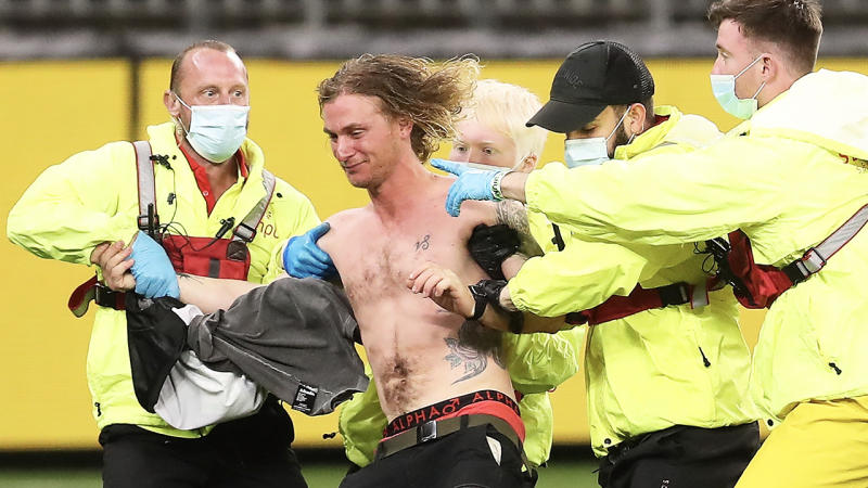 Victorian Jesse Hayen (pictured shirtless) being tackled by security.