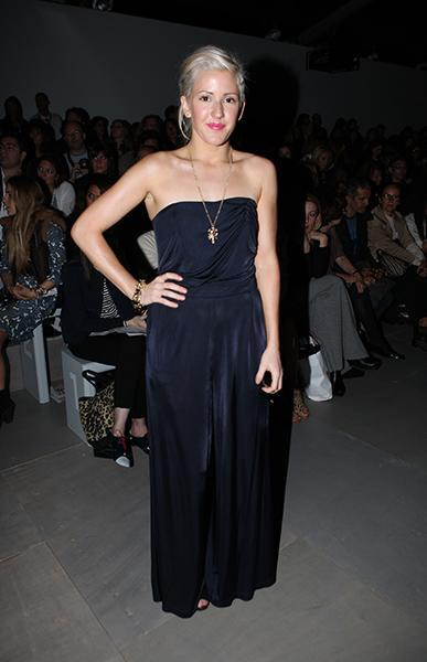 """<div class=""""caption-credit""""> Photo by: Getty Images</div><div class=""""caption-title"""">In the front row at Marios Schwab's S/S 2012 show</div>This is a much more comfortable and relaxed look for Ellie. The maxi jumpsuit is not an easy wardrobe piece to pull off, but by keeping her accessories simple (a long gold necklace and a single bracelet) she nails it. Plus, the swipe of bright magenta lip color is the perfect accent to any otherwise monochrome look."""