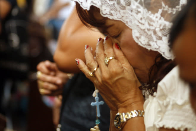 Dionisia Pacquiao (C), mother of Philippine boxing icon Manny Pacquiao, prays at a church in General Santos City, in southern island of Mindanao on June 10, 2012.  The Philippines was silenced June 10 after boxing superstar Manny Pacquiao was stunned by American challenger Timothy Bradley, losing his first bout in seven years.    AFP PHOTO/Paul BernaldezPAUL BERNANDEZ/AFP/GettyImages