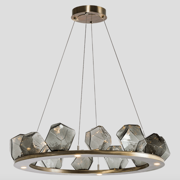 """<p>A fusion of bold geometry and organic warmth, the Gem Chandelier features LED-lit artisan glass that evokes the look of precious stones without the visual distraction of traditional filament lamping. </p><p>Danielle's A-List Anecdote:<em>""""Gem Ring Chandelier is a clean, edgy light fixture that would work really well in a funky powder room. It has a rock star element that would be amazing paired with a fantastic, slightly over the top wallpaper.""""</em></p><p><u>Learn More at <a href=""""https://studio.hammerton.com/"""" rel=""""nofollow noopener"""" target=""""_blank"""" data-ylk=""""slk:studio.hammerton.com"""" class=""""link rapid-noclick-resp"""">studio.hammerton.com</a>!</u></p>"""