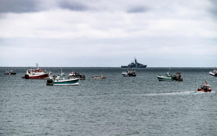 A British gunboat keeps an eye on the flotilla of fishing vessels seen outside St Helier harbour, Jersey, as French fishermen protest post-Brexit changes to fishing in the area - saltylens_ci / matt noel / SWNS