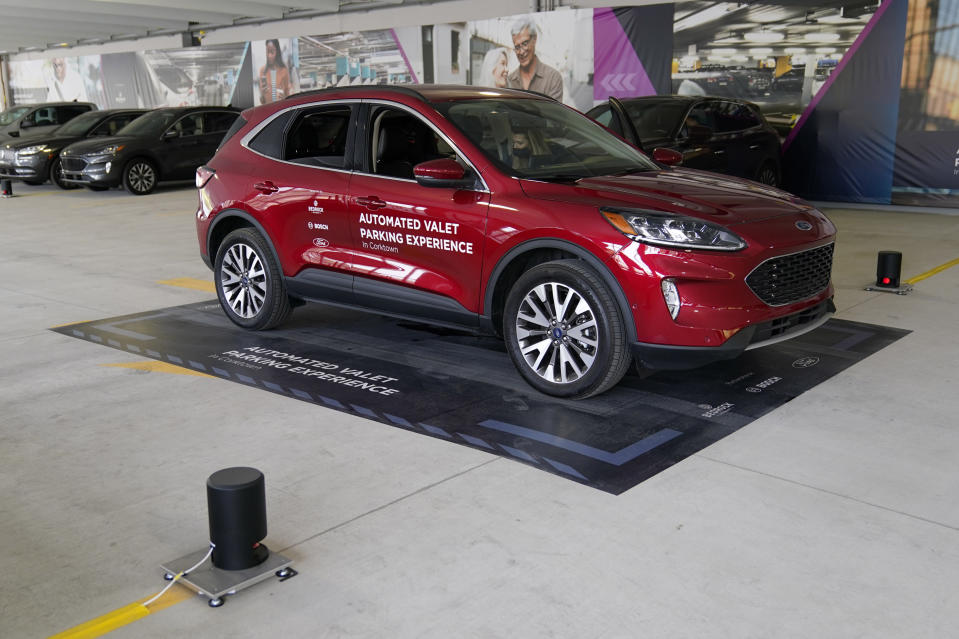 A Ford Escape is seen on a starting block before floor sensors help navigate the vehicle to self park, Tuesday, Aug. 25, 2020 in Detroit. Ford, Bosch and real estate company Bedrock are teaming up to test technology that will let vehicles park by themselves in parking decks. The companies are testing the technology using floor-mounted sensors and computers that can control mainly existing features in the Ford Escape. They say the technology is likely to arrive before widespread use of fully autonomous vehicles because sensors and computers inside parking decks can be used. (AP Photo/Carlos Osorio)