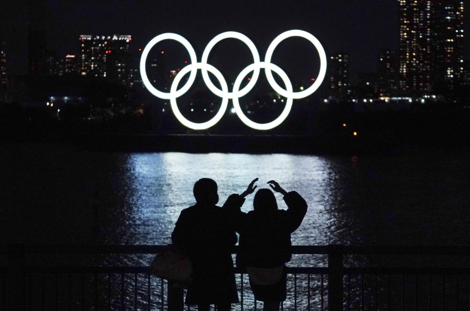 FILE - In this Dec. 1, 2020, file photo, a man and a woman look at the Olympic rings float in the water in the Odaiba section in Tokyo. Opposition to the Tokyo Olympics is growing with calls for a cancellation as virus cases rise in Japan. The International Olympic Committee and local organizers have already said another postponement is impossible, leaving cancellation, or going ahead, as the only options. (AP Photo/Eugene Hoshiko, File)