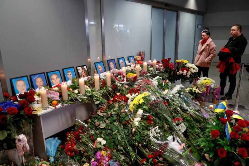 People mourn in front of a memorial for the flight crew members of the Ukraine International Airlines Boeing 737-800 plane that crashed in Iran, at the Boryspil International airport