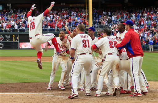 Philadelphia Phillies' Freddy Galvis leaps into the group of his teammates after hitting a game-winning solo-home run in the ninth inning of the MLB National League baseball game with the Cincinnati Reds, Sunday, May 19, 2013, in Philadelphia. The Phillies won 3-2. (AP Photo/Tom Mihalek)