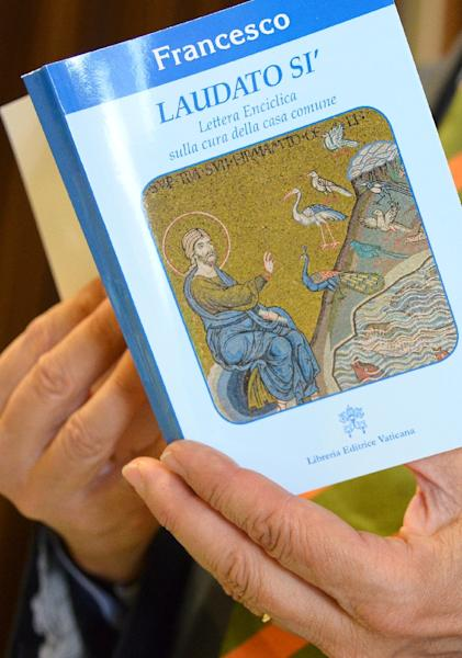 """A man holds a copy of Pope Francis's encyclical on climate change titled """"Laudato Si'"""" during the official presentation at the Vatican, on June 18, 2015 (AFP Photo/Vincenzo Pinto)"""
