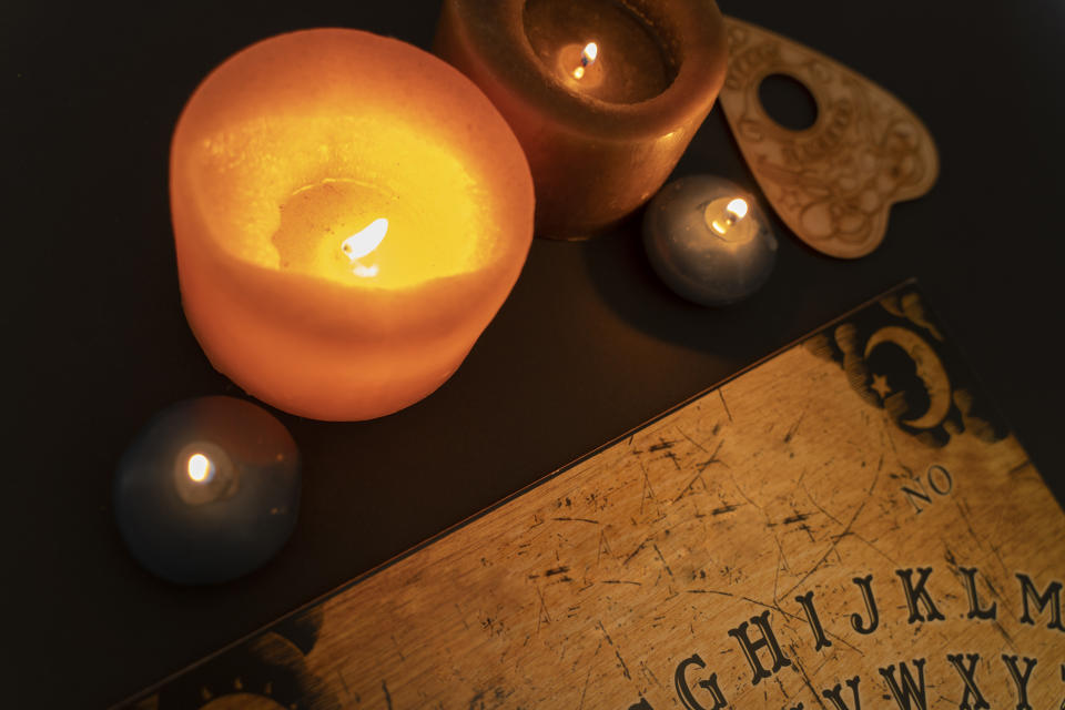 Above view of ouija board on dark background by candlelight