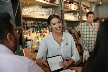 Rep. Alexandria Ocasio-Cortez (D-NY) speaks with people after taking an order in support of One Fair Wage at The Queensboro restaurant in New York