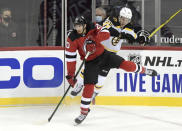 Boston Bruins defenseman Brandon Carlo (25) collides with New Jersey Devils center Michael McLeod (20) during the second period of an NHL hockey game Saturday, Jan. 16, 2021, in Newark, N.J. (AP Photo/Bill Kostroun)