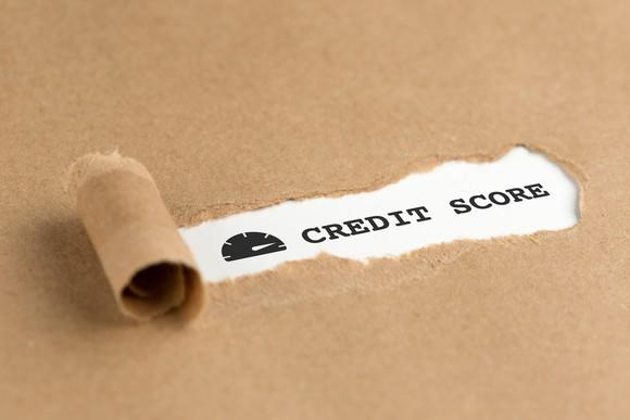 Paper being torn to reveal text that says Credit Score.