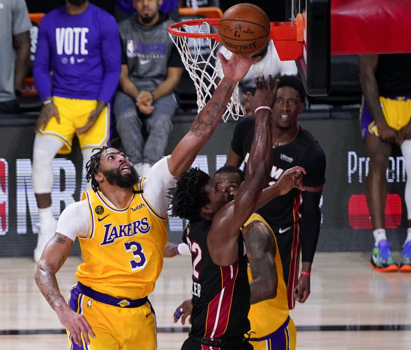 Lakers forward Anthony Davis blocks a shot by Heat forward Jimmy Butler late in the second half in Game 4 Tuesday night. (AP Photo/Mark J. Terrill)