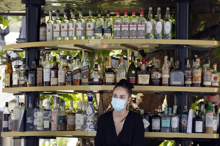 FILE - In this May 20, 2021, file photo, a bartender wears a mask while working at an outdoor bar amid the COVID-19 pandemic, at The Grove in Los Angeles. California workplace regulators are considering Thursday, June 3, 2021, whether to end mask rules if every employee in a room has been fully vaccinated against the coronavirus, frustrating business groups by eying a higher standard than the state plans to soon adopt for social settings. (AP Photo/Marcio Jose Sanchez, File)
