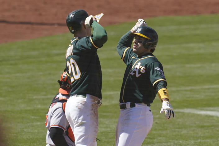 Oakland Athletics' Ramon Laureano, right, celebrates after hitting a two-run home run that scored Mark Canha, left, during the eighth inning of a baseball game against the Baltimore Orioles in Oakland, Calif., Sunday, May 2, 2021. (AP Photo/Jeff Chiu)