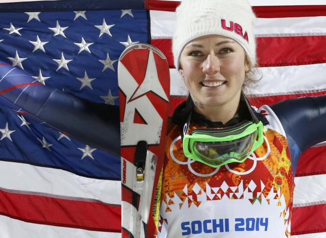 First-placed Mikaela Shiffrin of the U.S. poses with a U.S. flag after the flower ceremony for the women's alpine skiing slalom event at the 2014 Sochi Winter Olympics at the Rosa Khutor Alpine Centre, February 21, 2014. REUTERS/Leonhard Foeger (RUSSIA - Tags: OLYMPICS SPORT SKIING)