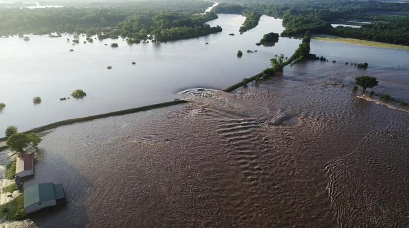In this aerial image provided by Yell County Sheriff's Department water rushes through the levee along the Arkansas River in Dardanelle, Ark., on Friday, May 31, 2019. Officials say the levee breached early Friday at Dardanelle, about 60 miles northwest of Little Rock. (Yell County Sheriff's Department via AP)