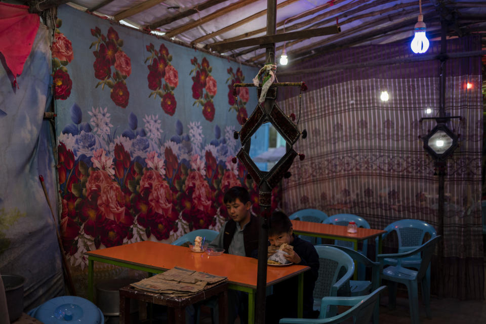 Two boys eat at a local restaurant in Kabul, Afghanistan, Friday, Sept. 10, 2021. (AP Photo/Bernat Armangue)