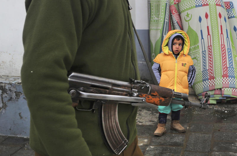 FILE- In this, Nov. 10, 2019 file photo, an Indian policeman guards as a Kashmiri child looks on outside the Hazratbal shrine, on the occasion of the Prophet's birth anniversary in Srinagar, India. On Nov. 10, all roads leading to Dargah Hazratbal, the region's most revered shrine, were sealed with pools of concertina wire on the yearly celebration of the birth anniversary of Prophet Muhammad. During previous years, the shrine would remain jam-packed with devotees from across Kashmir. This time, however, only neighborhood locals were allowed to offer prayers. (AP Photo/ Mukhtar Khan, File)