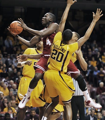 Indiana's Victor Oladipo (4) attempts to drive between Minnesota defenders Austin Hollins (20) and Rodney Williams, back, during the first half of an NCAA college basketball game on Sunday, Feb. 26, 2012, in Minneapolis. (AP Photo/Tom Olmscheid)