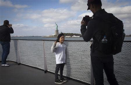 A father takes a photo of his daughter on the ferry coming back from the Statue of Liberty in New York, October 13, 2013. REUTERS/Carlo Allegri