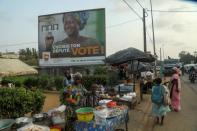 People move next to an awarness campaign billboard ahead of the legislative election in Abidjan