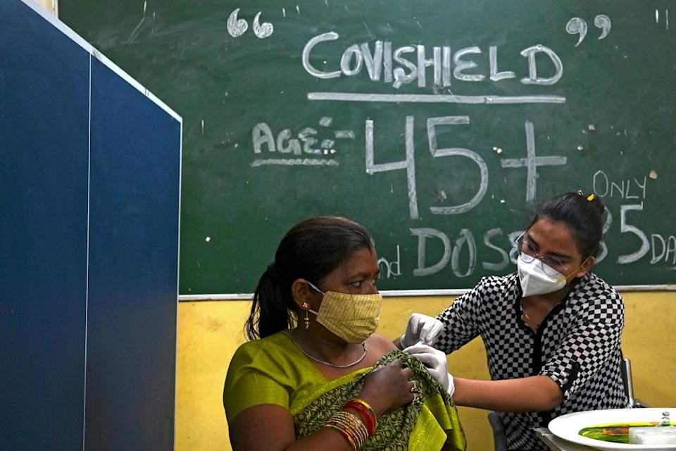 A health worker inoculates a woman with a jab of Covishield's Covid-19 Coronavirus vaccine at a vaccination Centre in New Delhi on June 21, 2021 after India opened up free vaccinations to all adults in an attempt to bolster its inoculation drive. (Photo by Money SHARMA / AFP) (Photo by MONEY SHARMA/AFP via Getty Images)