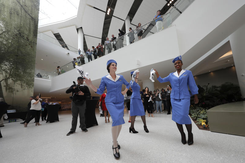 CORRECTS CITY TO KENNER, NOT BATON ROUGE- Women dressed as flight attendants dance and wave handkerchiefs to a second line parade during festivities for the opening of the newly built main terminal of the Louis Armstrong New Orleans International Airport in Kenner, La., Tuesday, Nov. 5, 2019. (AP Photo/Gerald Herbert)